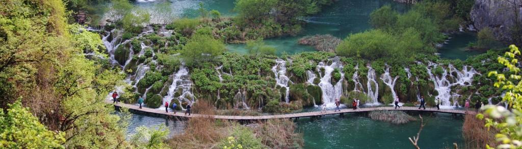 Water path in Plitvice park, Croatia with beautiful waterfall behind it